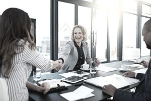 Shot of two corporate businesswomen shaking hands during a meeting in the boardroom