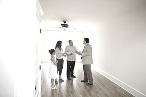 Family with realtor in new hom