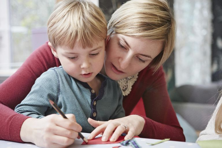 Mother and son drawing at kitchen table