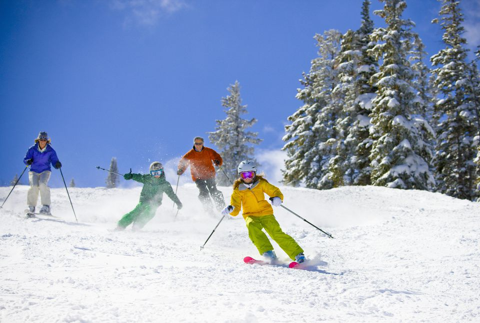 A family skiing down the side of a mountain.