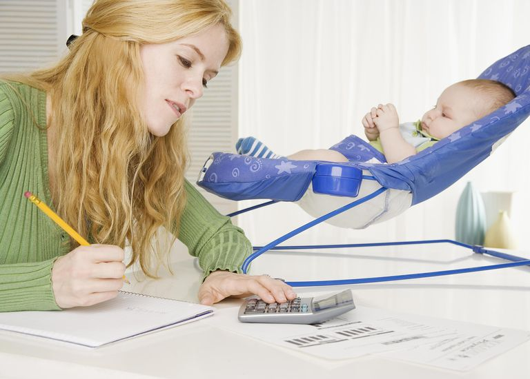 Mother using calculator with baby in seat on table