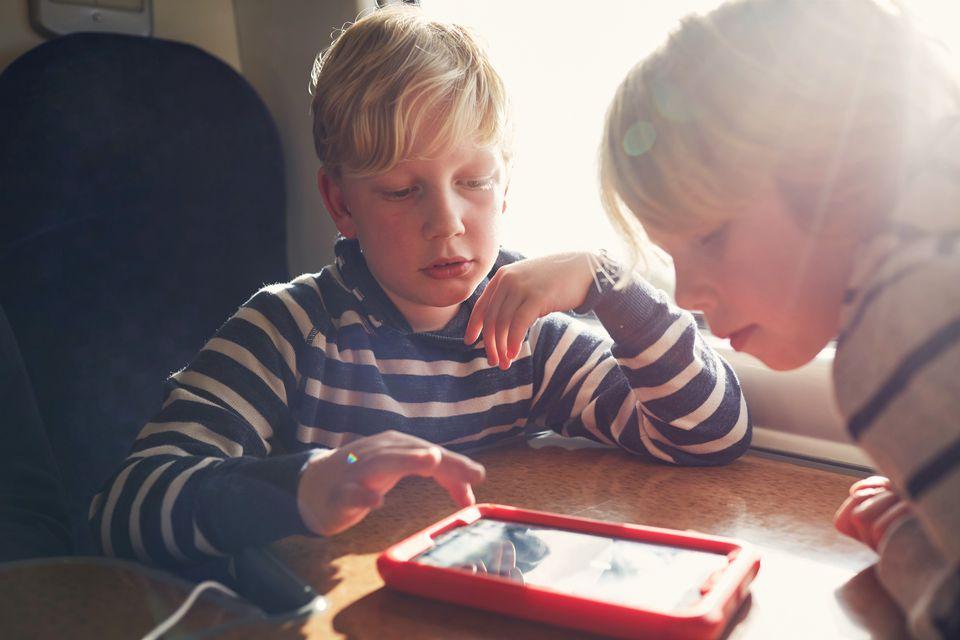 Children using a digital tablet on a train