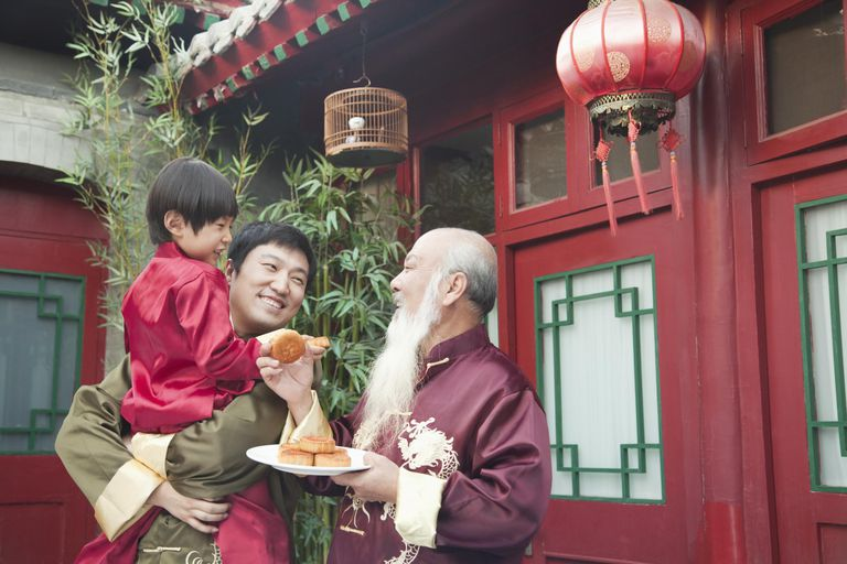 Chinese family sharing plate of food outdoors