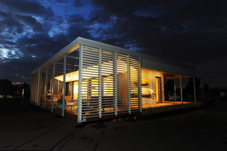 Solar home at dusk, lights seen through louvers
