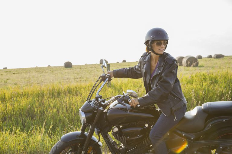 Woman sitting on motorcycle outdoors