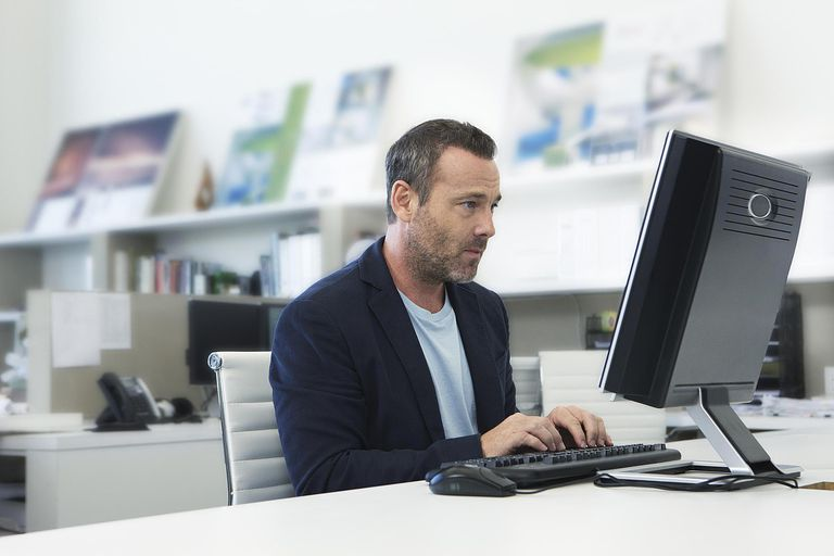 Older man working on computer in small modern offi