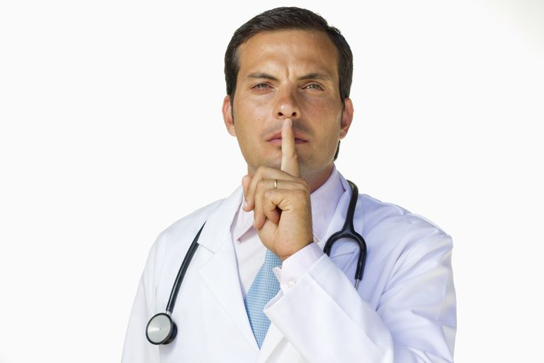 """Male physician with his finger across his lips saying """"Shhh."""""""