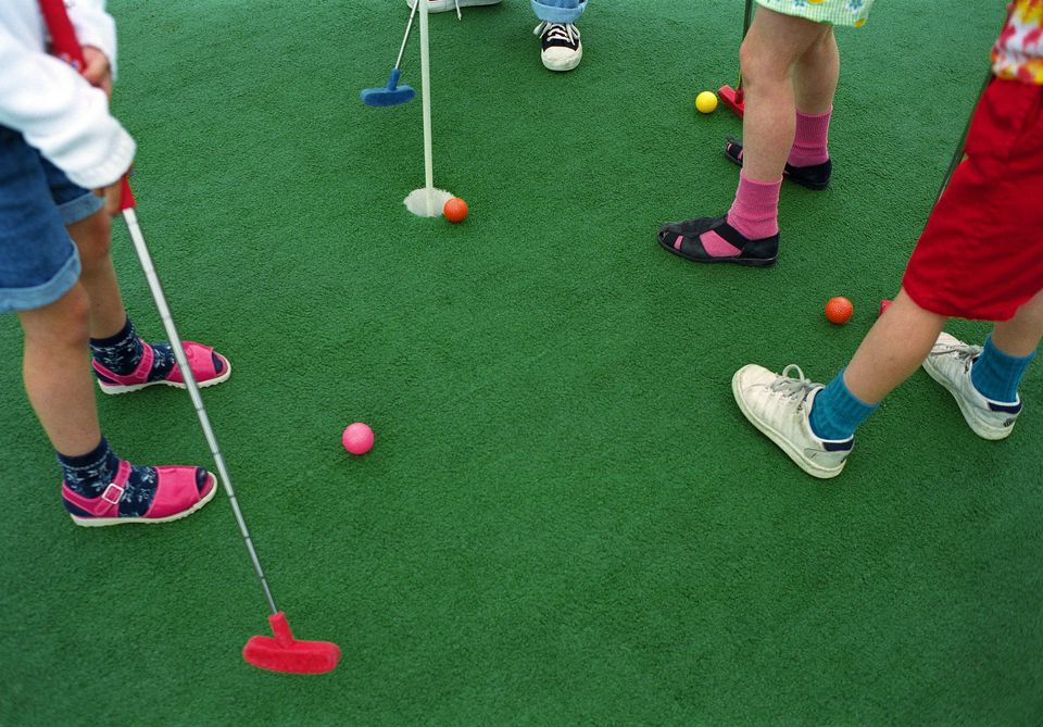 Children (7-10) playing miniature golf, low section (Enhancement)