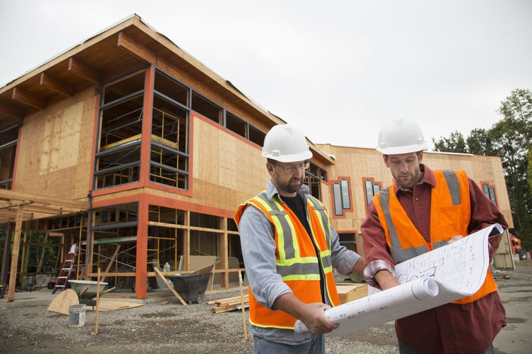 Two workers reviewing building plans