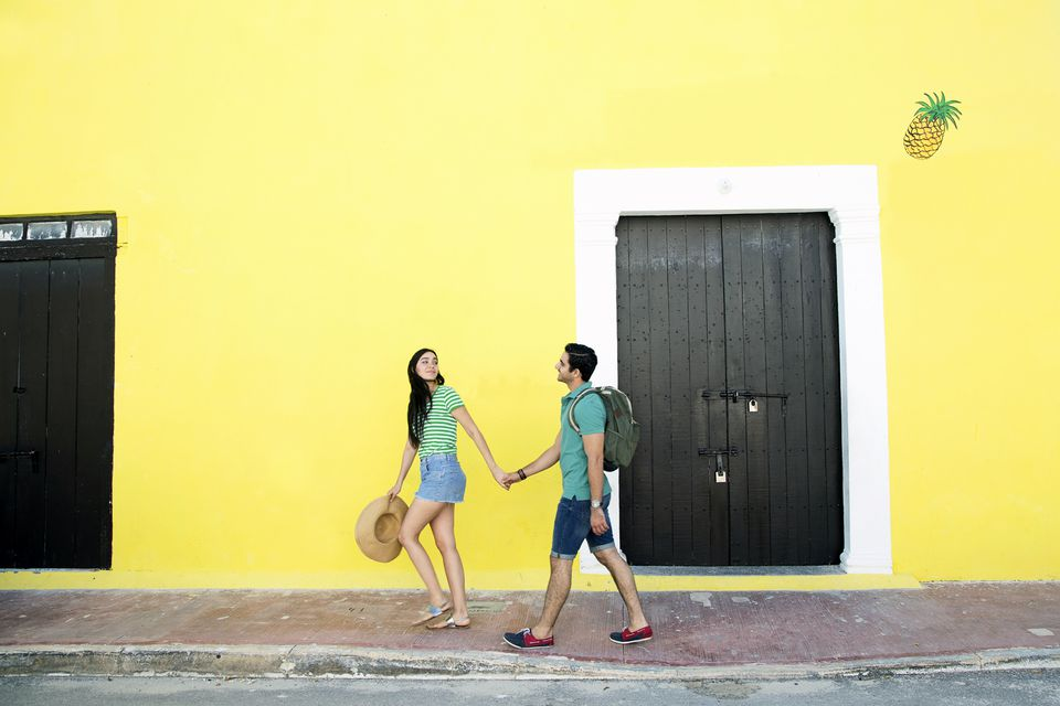 Couple holding hands walking past yellow wall in Mexico