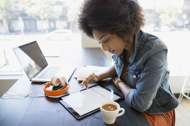 focused woman working at digital tablet - How To Address A Cover Letter