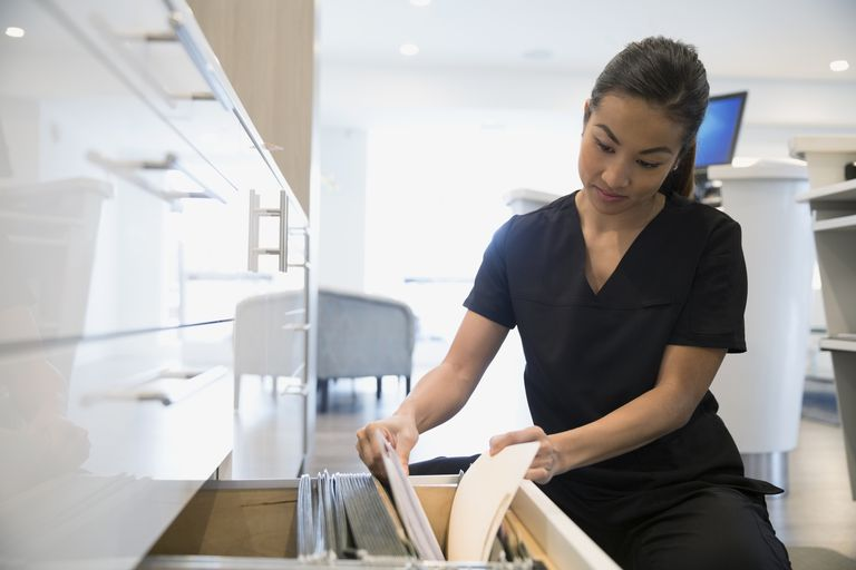Nurse reviewing medical record in clinic filing cabinet