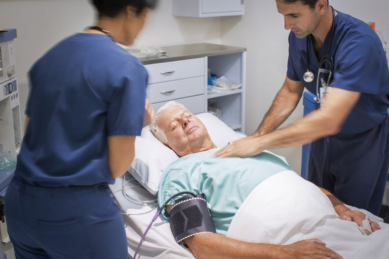 Doctor performing CPR on unconscious patient in emergency room