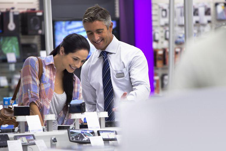 Smiling salesman showing woman digital cameras in electronics.