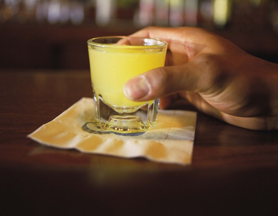 Person holding shot glass at bar