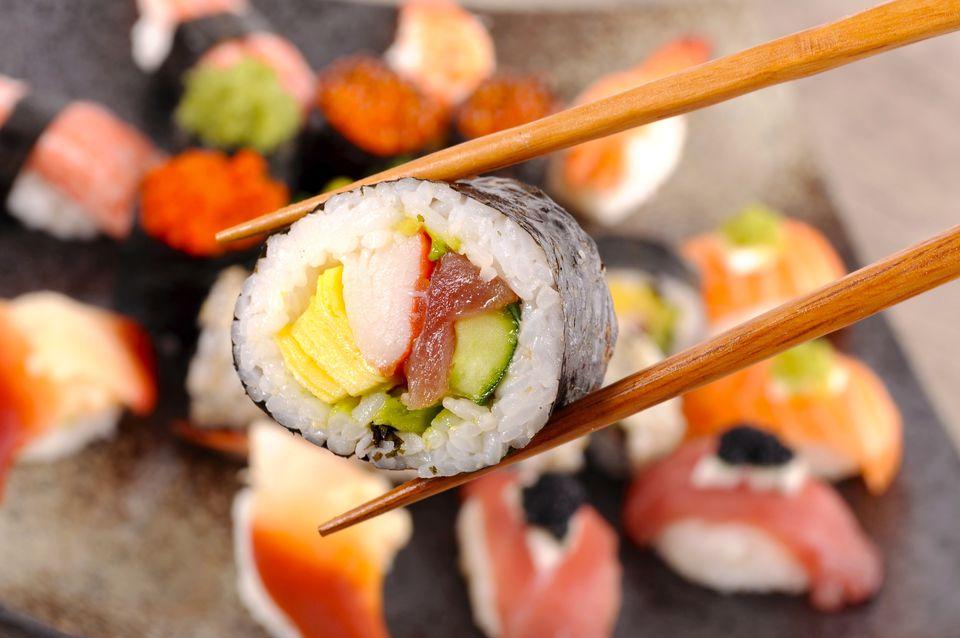 A close-up of a futomaki between chopsticks