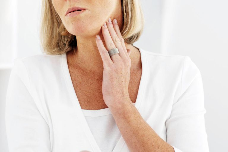 Front view of mature woman holding pills and rubbing her neck with pain