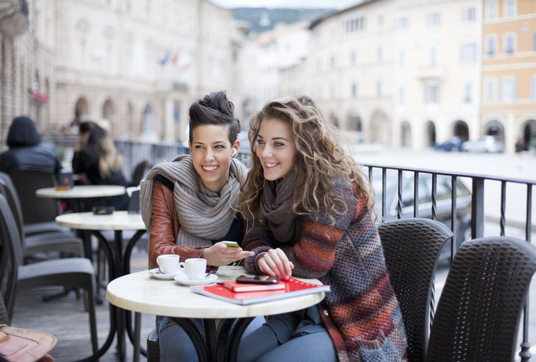 two teenage girls at a café, sharing mp3-player