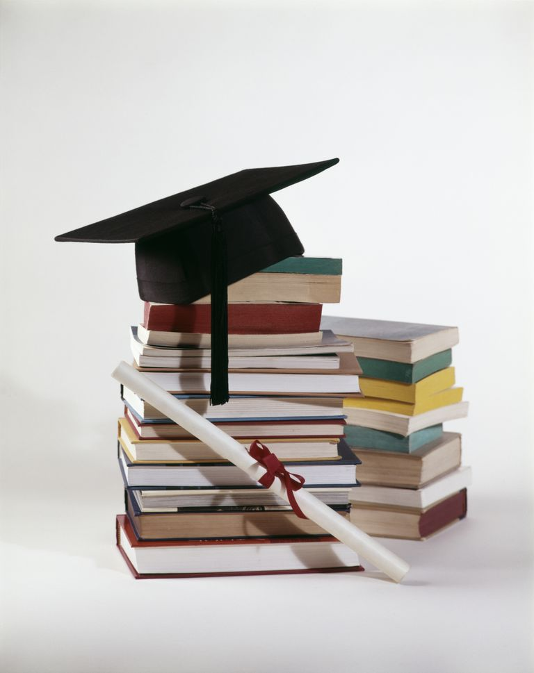 1970s GRADUATION STILL LIFE OF DIPLOMA AND MORTARBOARD ON TOP OF PILE STACK OF BOOKS