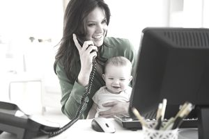 Woman on phone and computer with a baby on her lap