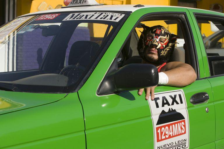 A wrestler driving a taxi