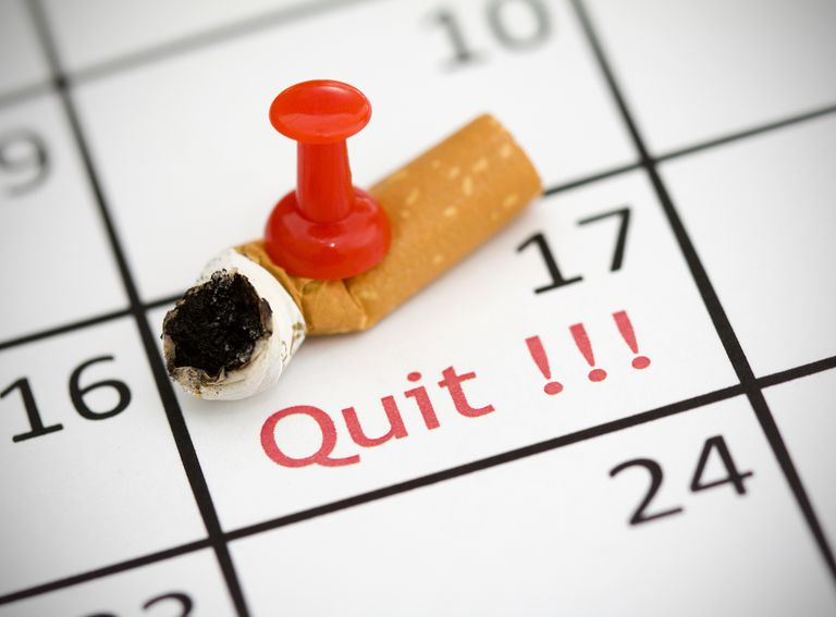 Cigarette butt pinned onto a calendar date marked quit