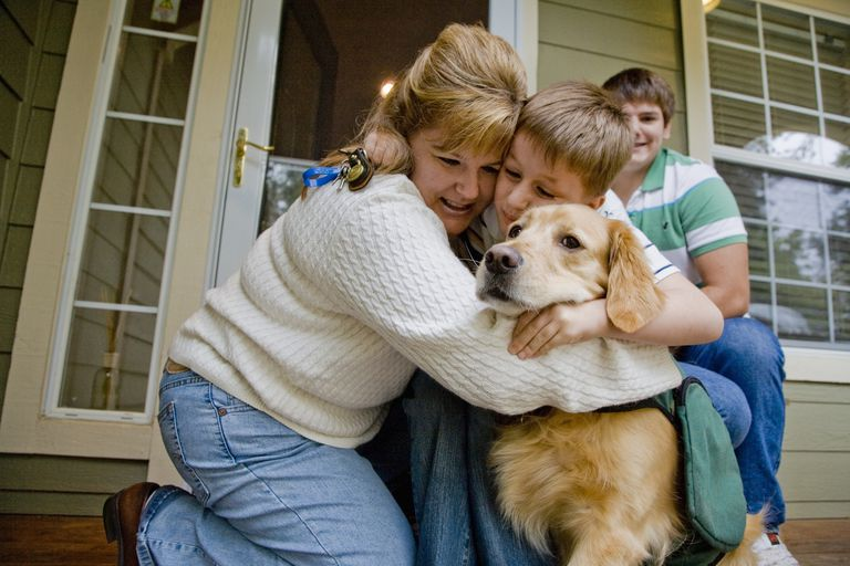 Mom hugging autistic son and dog