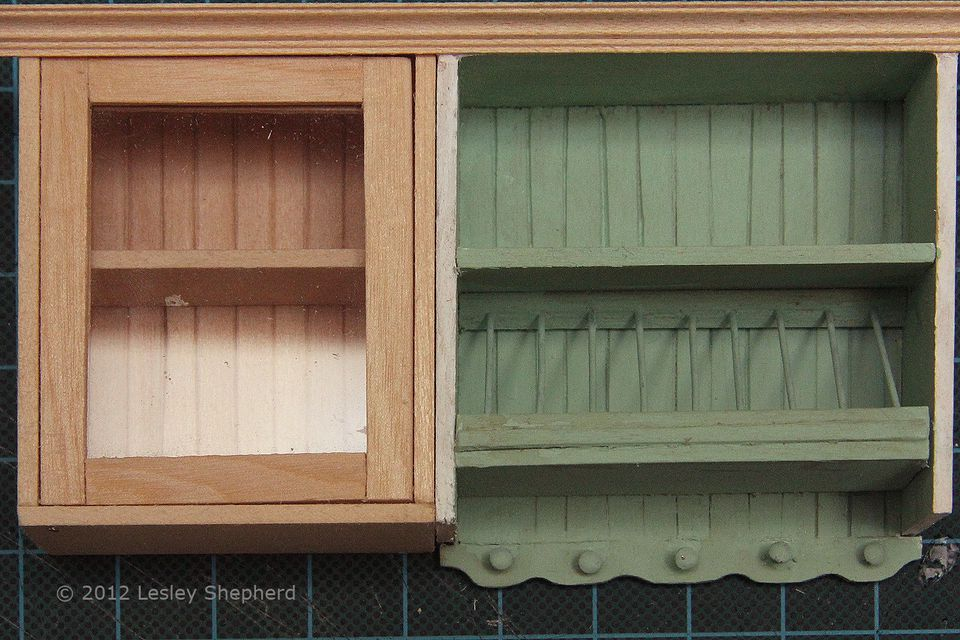 Glass fronted upper cabinet with opening door for a dollhouse scale kitchen.
