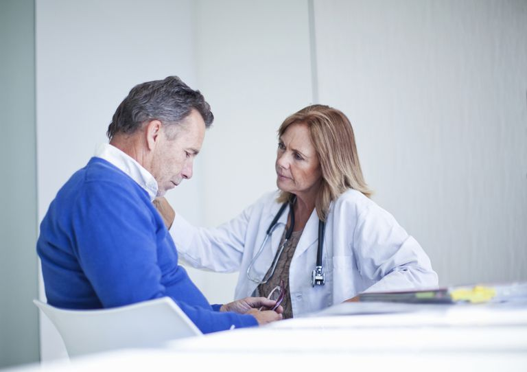 Mature female doctor sympathizing with patient