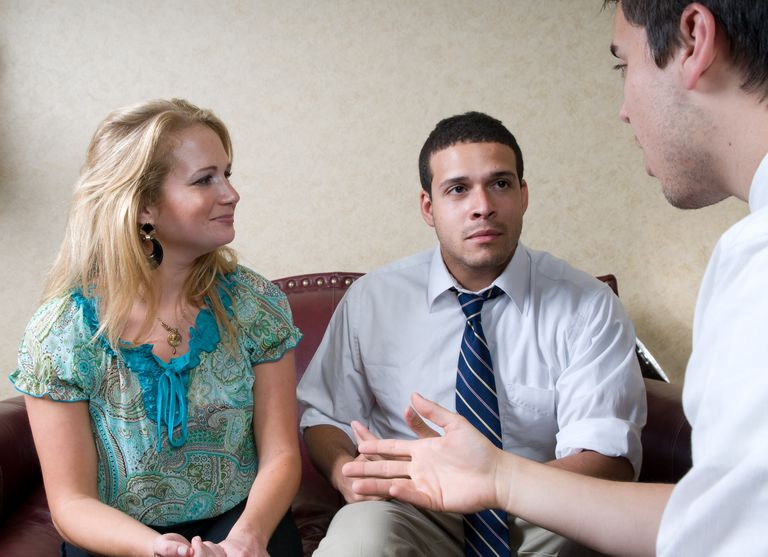 Mediator speaking to a young couple.