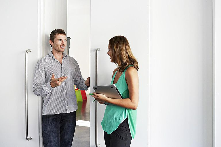 man and woman talking outside of an office