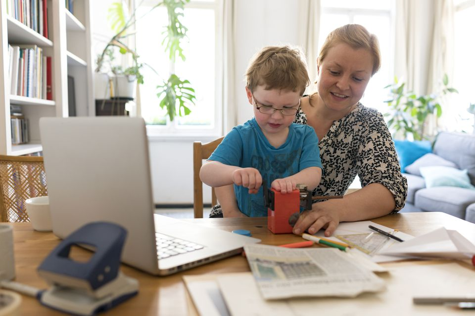 Mother working at home with toddler son on her lap