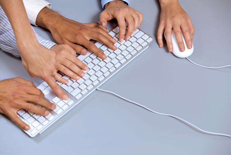 Human hands on computer keyboard with one hand using computer mouse