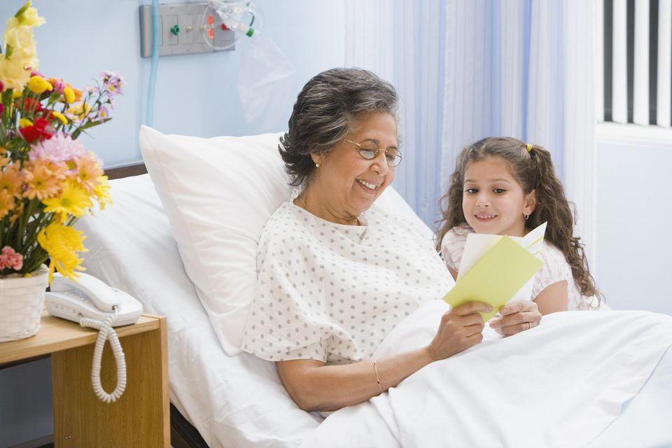Hispanic girl giving card to grandmother in hospital bed