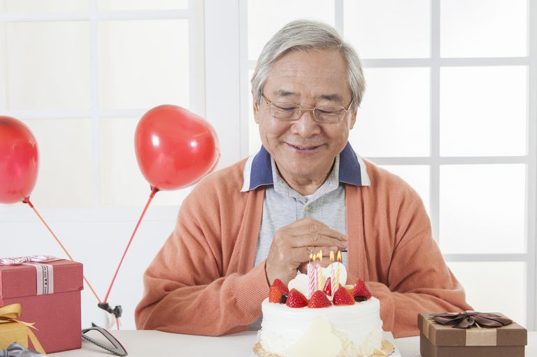 Senior man celebrating birthday and making a wish with eyes closed,