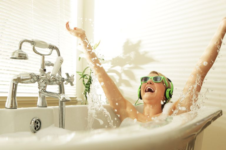 A woman wearing green sunglasses and headphones splashing around in a bathtub