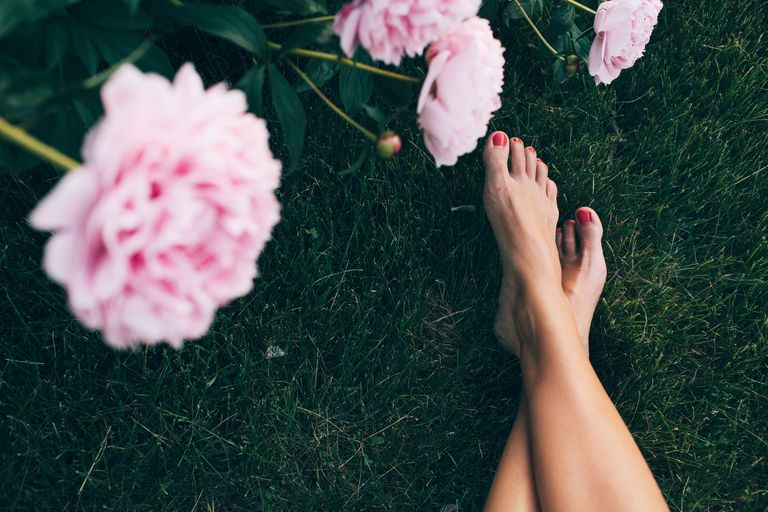 Barefeet outside by flower plant