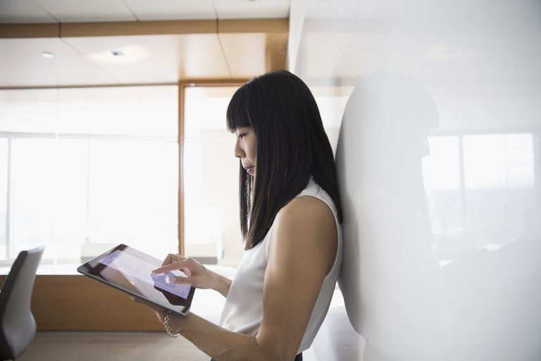 Businesswoman using digital tablet at whiteboard in conference room