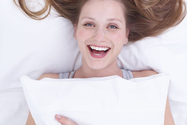 A smiling woman holds a pillow.