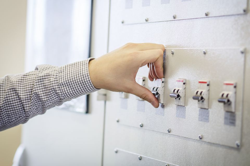 engineer switches on circuit breaker in electric switchboard