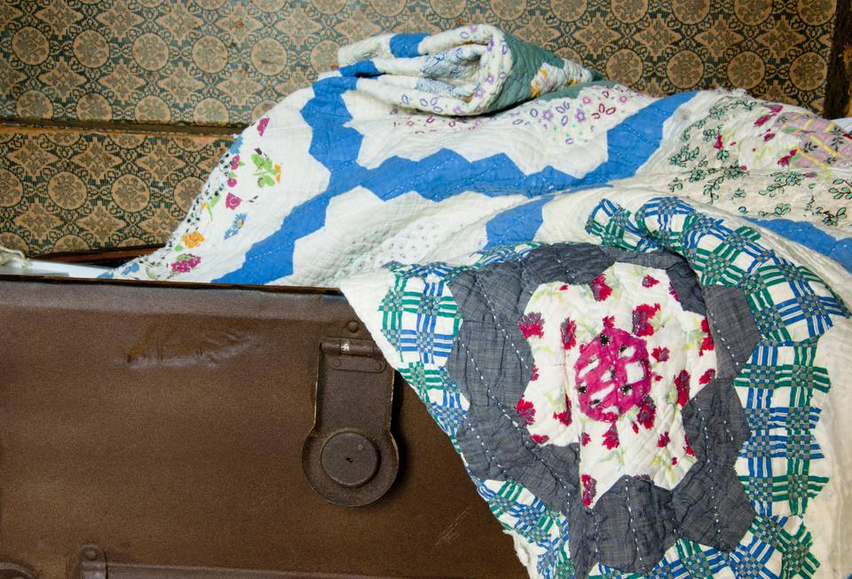 Old quilt lays in an antique trunk.