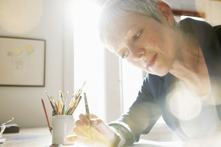mature woman painting in studio