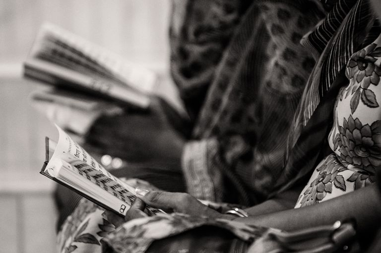 Close-Up Of Women Holding Holy Book
