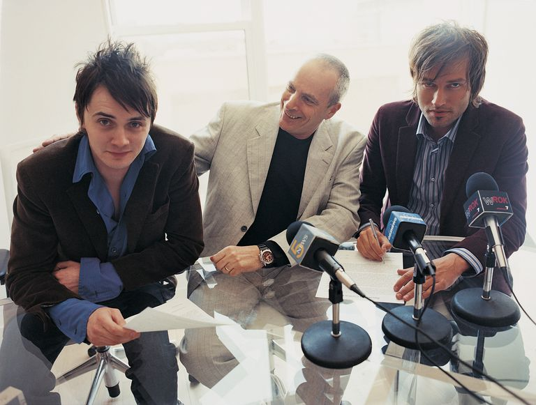 Pop Musicians Signing a Contract at a News Conference With Their Manager