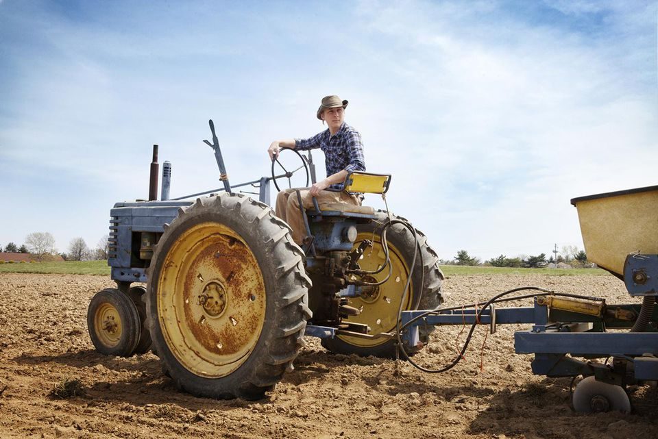 Young man sitting on a tractor in a field