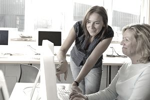 Woman helping mature woman in computing class, pointing at screen