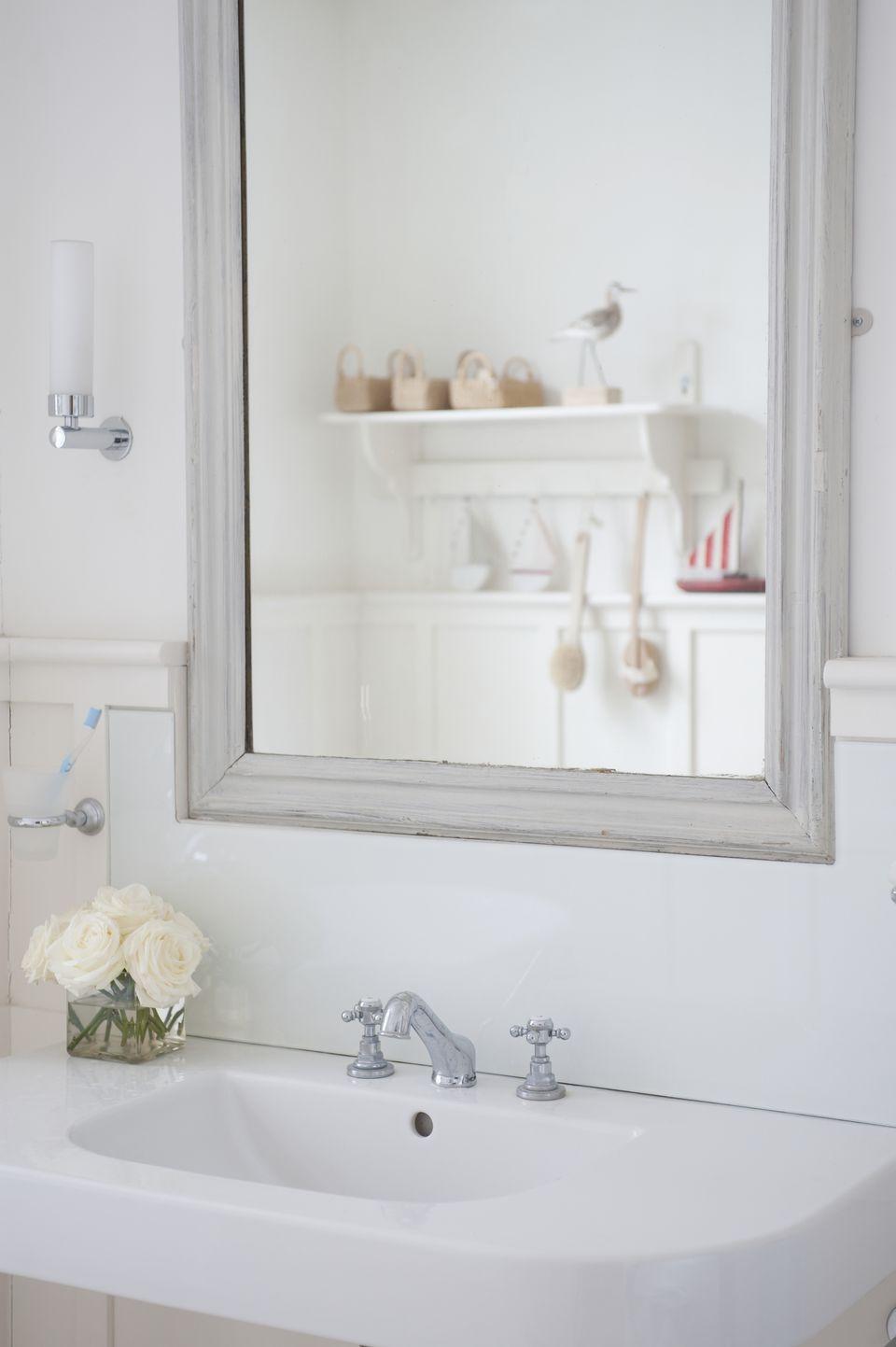 Grey painted mirror surround above washbasin, London
