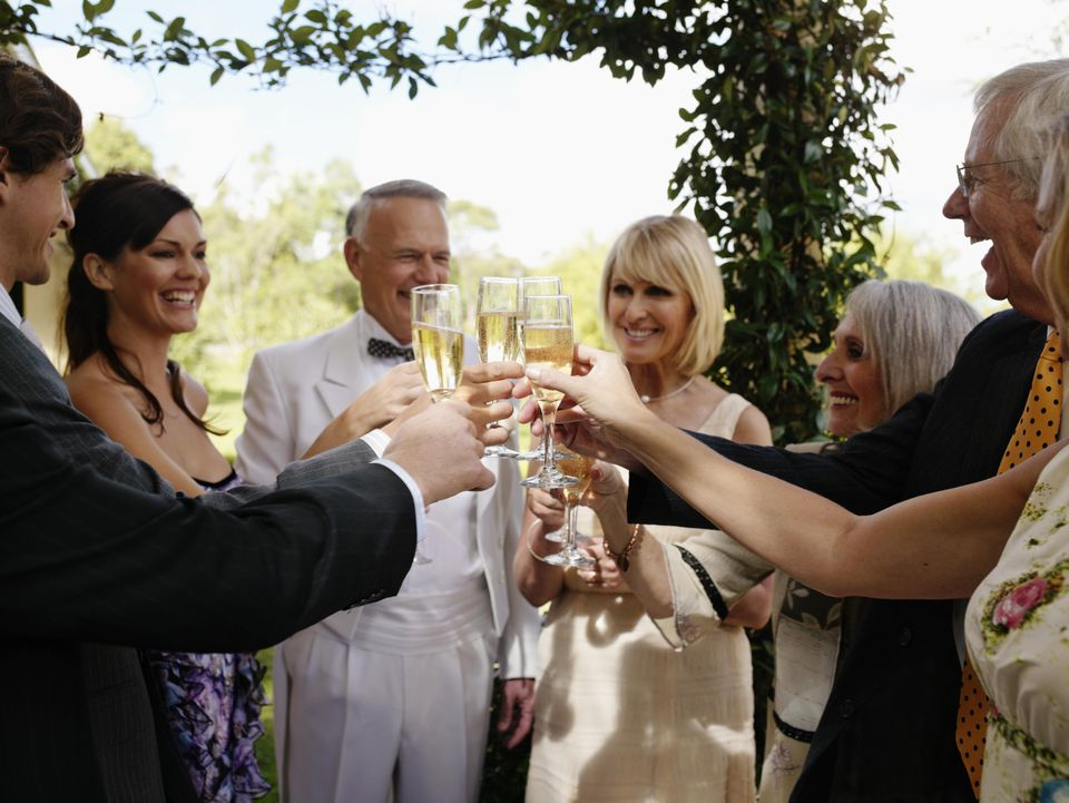 Bride and groom toasting with champagne and guests