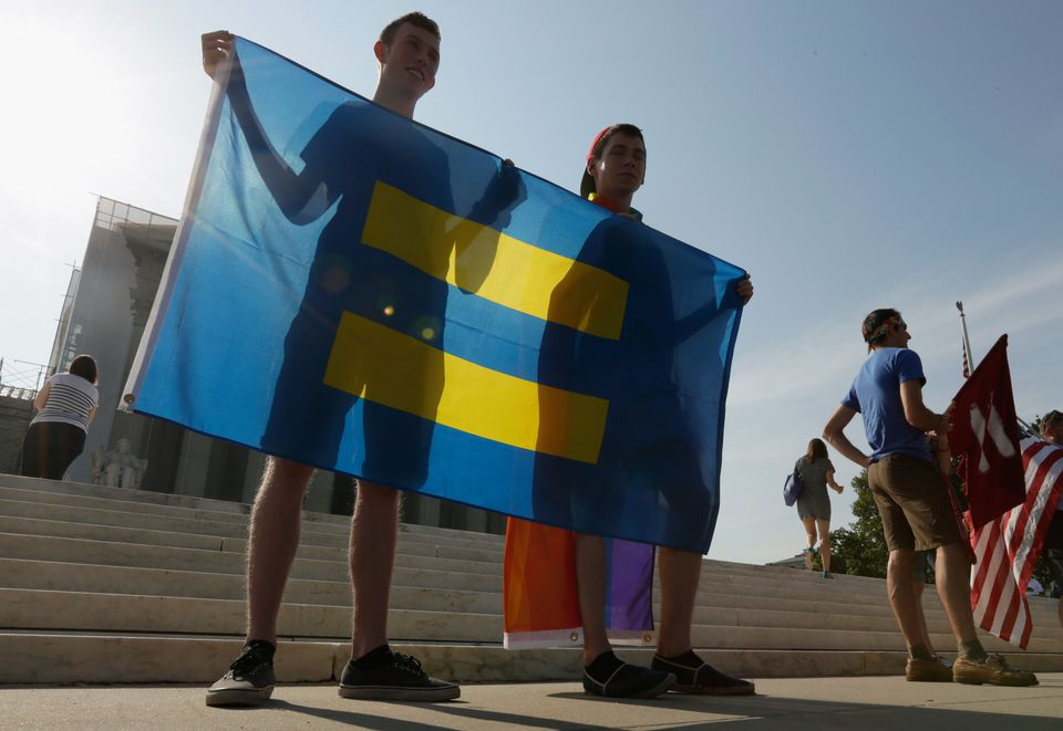 two young men holding up a flag for Gay rights