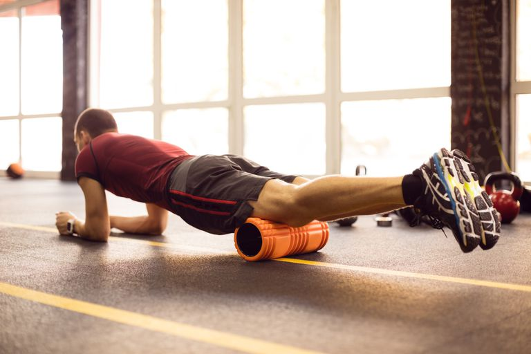 man using foam roller for self-massage in gym